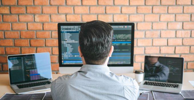 uomo seduto al pc con tre schermi davanti